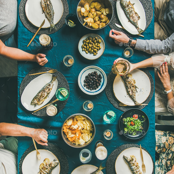 Flat-lay of people eating fish and drinking beer, square crop - Stock Photo - Images