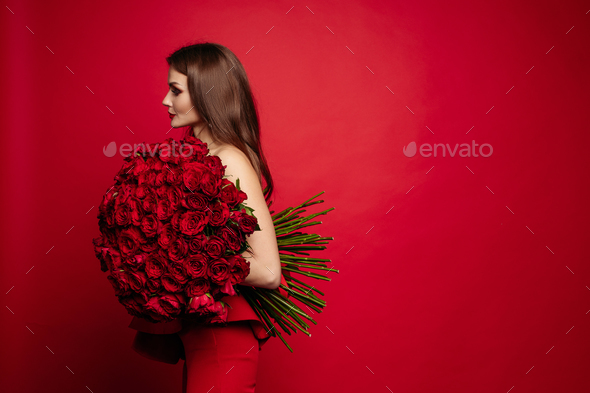 Gorgeous woman in red dress keeping bouquet of roses - Stock Photo - Images