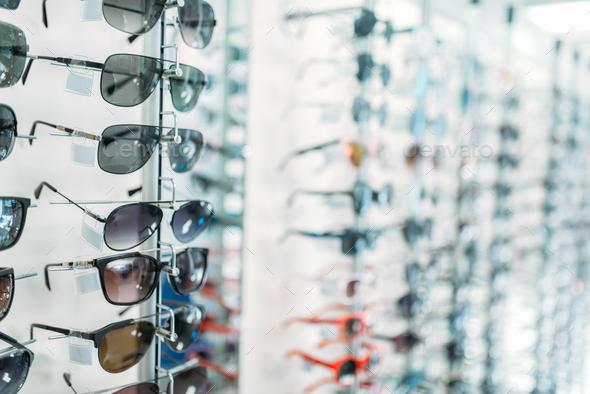 Eyeglasses and sunglasses showcase in optic shop - Stock Photo - Images