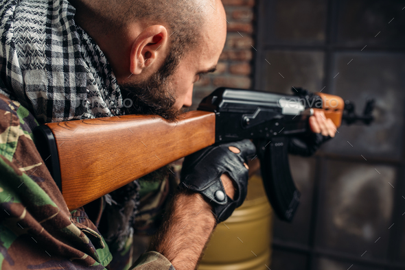 Cruel terrorist aiming from a rifle closeup - Stock Photo - Images