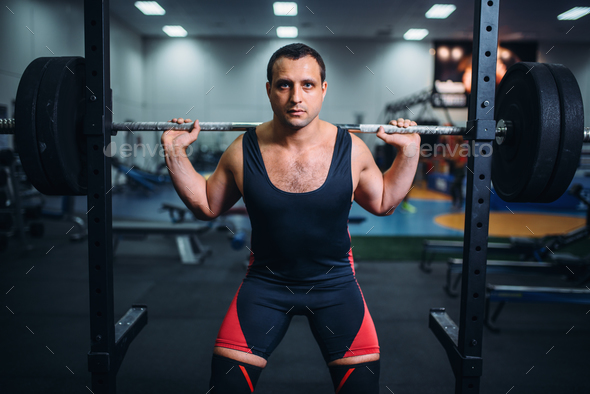 Athlete prepares to make squats with barbell - Stock Photo - Images
