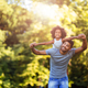 Portrait of young father carrying his daughter on his back - PhotoDune Item for Sale