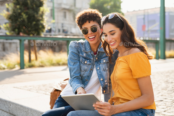 Two women using digital tablet outdoor - Stock Photo - Images