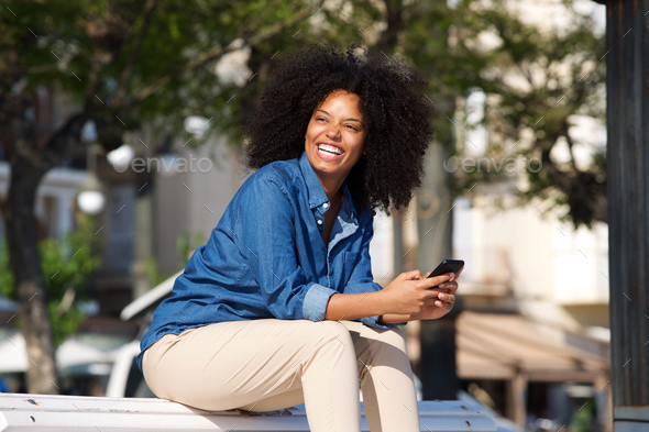 Cheerful woman sitting outside with mobile phone - Stock Photo - Images