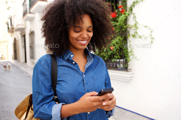 Smiling woman walking on street with mobile phone - Stock Photo - Images