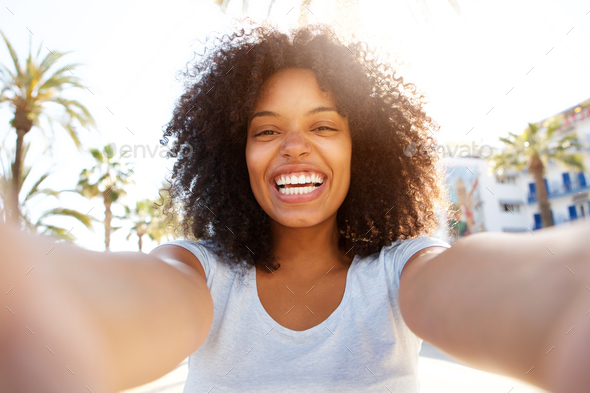 Selfie of laughing black woman outside with curly hair - Stock Photo - Images