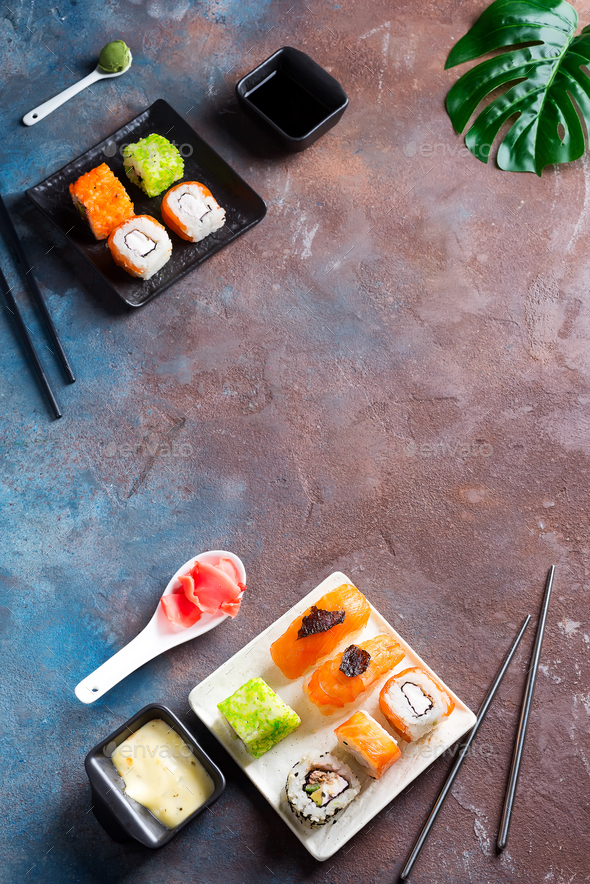 Various Fresh and delicious sushi set on black slate with slate sticks, sauce and nori on duotone - Stock Photo - Images
