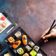 Various Fresh and delicious sushi set on white slate , hand with slate sticks, sauce on light stone - PhotoDune Item for Sale