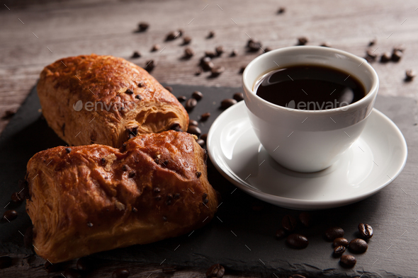 Mug of coffee with delicious pastry and spreaded beans of coffee - Stock Photo - Images