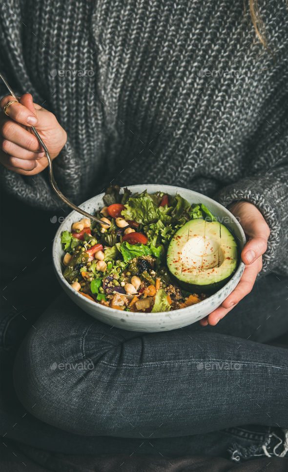 Woman sitting and eating healthy vegetarian dinner from Buddha bowl - Stock Photo - Images