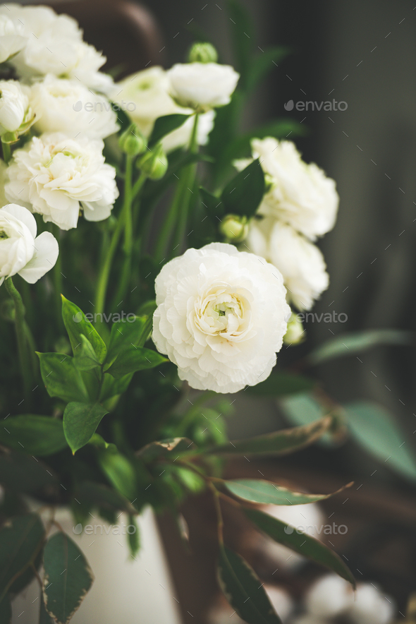 Spring white buttercup flowers in enamel jug, curtain behind - Stock Photo - Images
