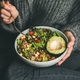 Woman sitting and eating healthy vegetarian dinner from Buddha bowl - PhotoDune Item for Sale