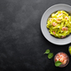 Boiled fettuccine pasta with fresh spinach pesto and shrimps on black background. Italian cuisine - PhotoDune Item for Sale