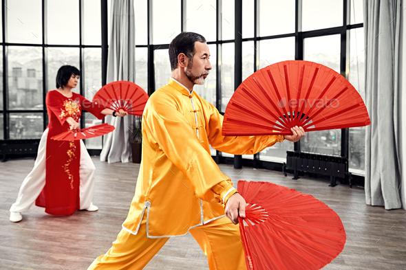 Couple of senior masters practicing qi qong taijiquan - Stock Photo - Images