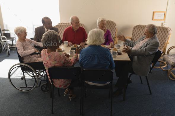 Group Of Happy Senior Friends Having Breakfast On Dining Table At Nursing Home Stock Photo By Wavebreakmedia