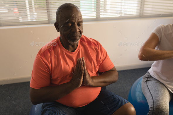 Front view of active senior men performing yoga, relaxing with ball exerciceat home - Stock Photo - Images
