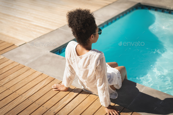 Young  woman with sunglasses sitting at poolside in backyard of home on a sunny day - Stock Photo - Images