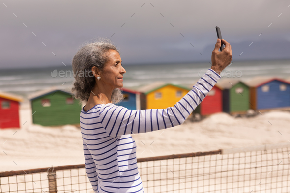 Side view of senior woman taking selfie with mobile phone on promenade at beach - Stock Photo - Images