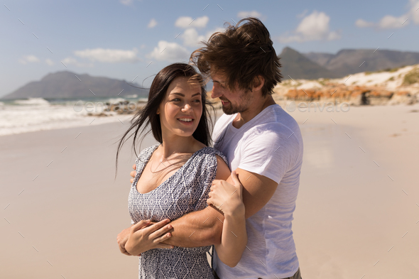 Side view of romantic happy young couple embracing on beach in the sunshine - Stock Photo - Images
