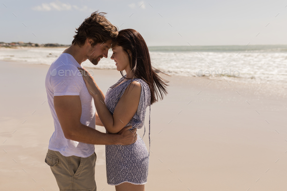Side view of romantic happy young couple head to head on beach in the  sunshine