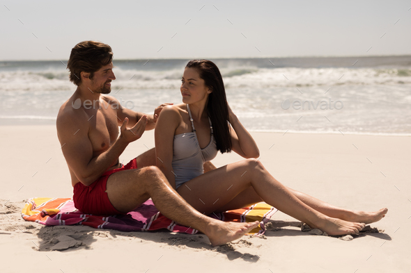 Side view of happy young man applying sunscreen lotion on woman back at beach in the sunshine - Stock Photo - Images