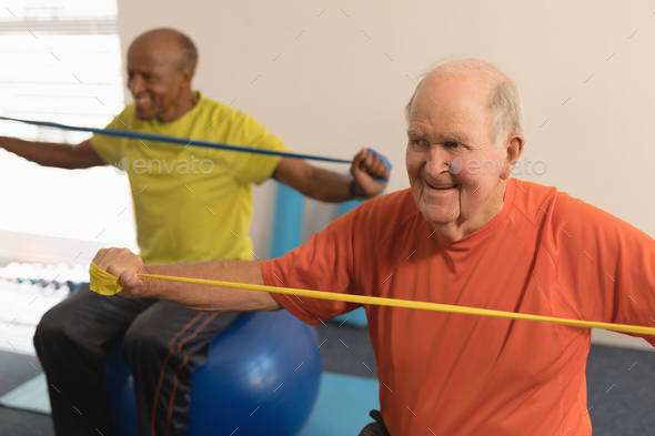 Front view of senior man exercising with resistance band in fitness studio - Stock Photo - Images