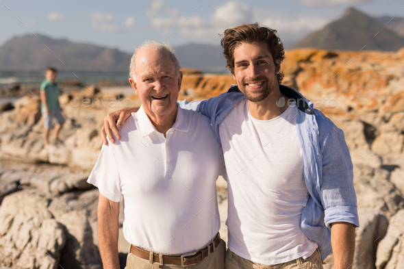 Front view of happy father and son with arms around looking at camera on beach - Stock Photo - Images
