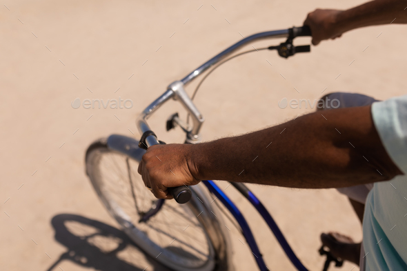 Mid section of senior man riding bicycle on beach in the sunshine