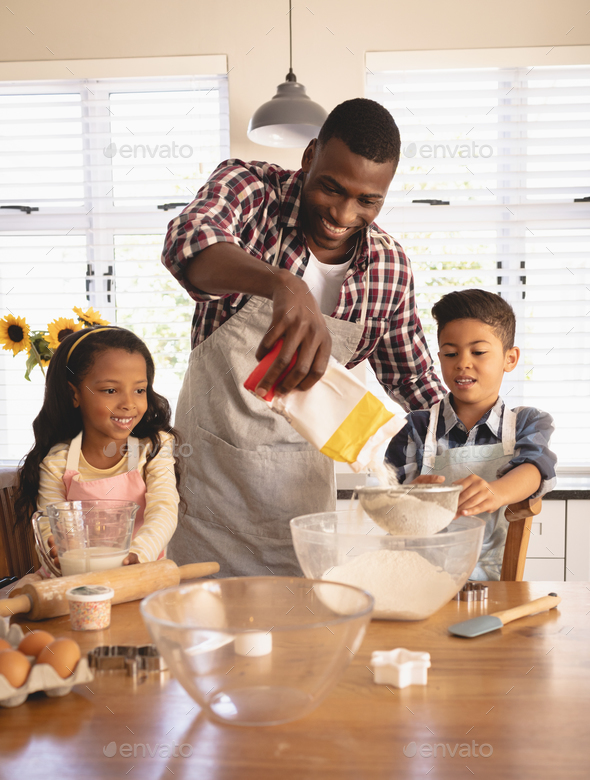 Front view of African American father and children baking cookies in kitchen at home - Stock Photo - Images
