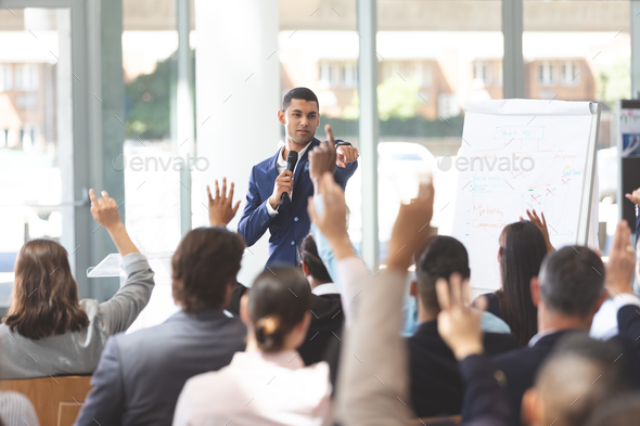 Young businessman speaking at business seminar with diverse group of people raising their hand - Stock Photo - Images