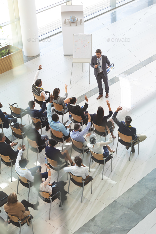Group of diverse business people raising their hands to ask questions to businessman at conference - Stock Photo - Images