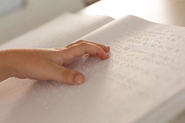 Close-up of a blind boy hand reading a braille book in classroom at  elementary school