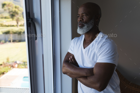 Thoughtful senior African American man looking through window with crossed arms at home - Stock Photo - Images