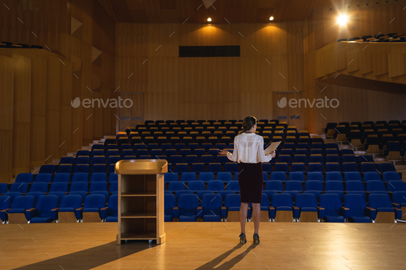 Businesswoman practicing and learning script while standing in the auditorium - Stock Photo - Images