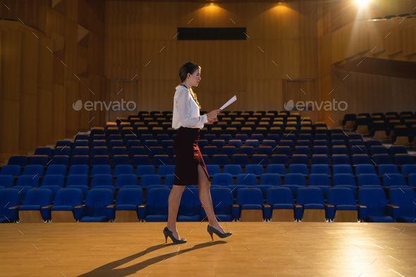 Businesswoman practicing and learning script while walking in the auditorium - Stock Photo - Images