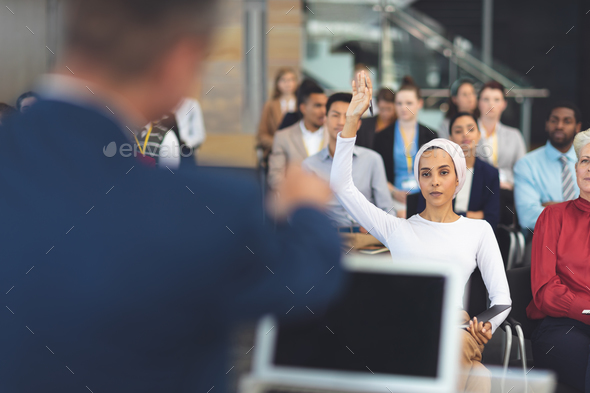 Front view of mixed race businesswoman raising hand at a business seminar in modern office building - Stock Photo - Images