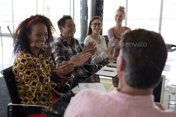 Side view of young multi-ethnic business colleagues applauding businessman in modern office - Stock Photo - Images