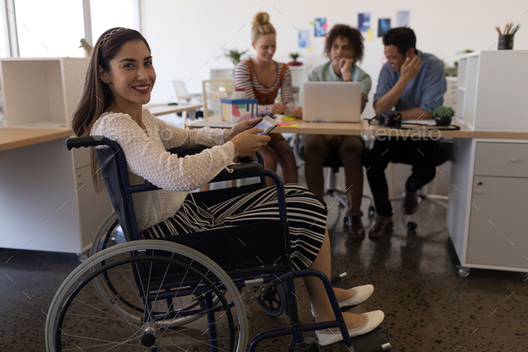 Pretty disabled mixed-race female smiling at the camera in the office.  - Stock Photo - Images