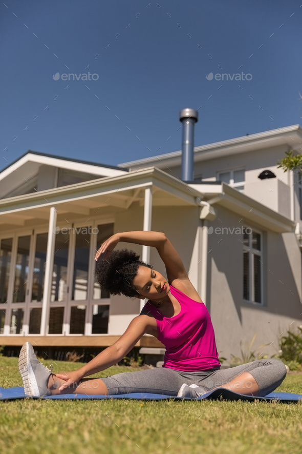 Beautiful young fit mixed-race woman performing stretch exercise - Stock Photo - Images