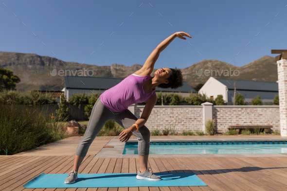 Young African American woman performing stretching exercise next to the swimming pool  - Stock Photo - Images
