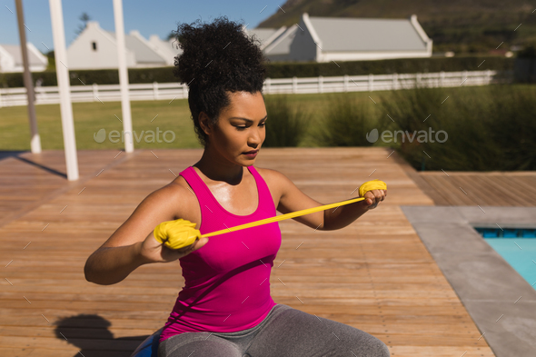 Beautiful young African American woman exercising with resistance band in the backyard - Stock Photo - Images