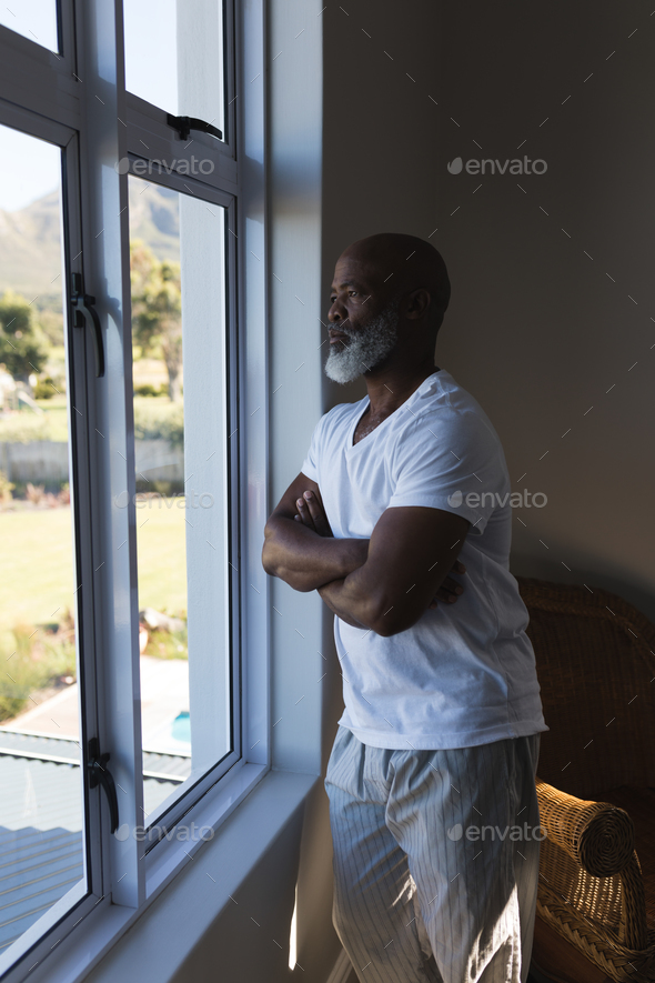 Thoughtful handsome senior African American man looking through the window witch crossed arms  - Stock Photo - Images