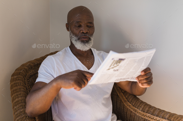 Front view of a handsome senior African American man reading newspaper on a wicker chair at home - Stock Photo - Images
