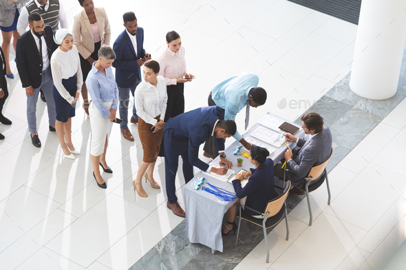 High angle view of diverse business people checking in at conference registration table in  lobby - Stock Photo - Images