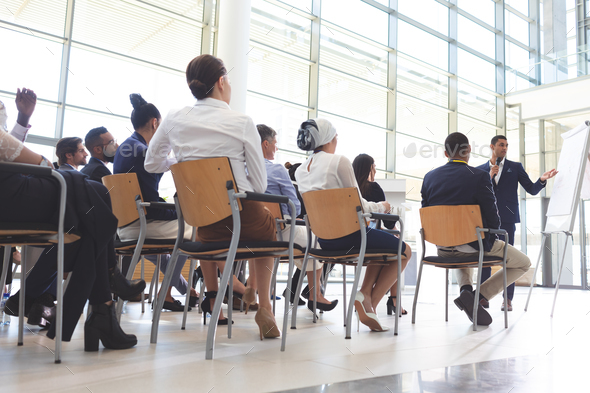 Businessman showing information on flip chart to group of diverse business people in conference room - Stock Photo - Images
