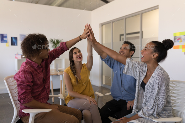Business colleagues giving high five to each other after successful meeting in modern office - Stock Photo - Images