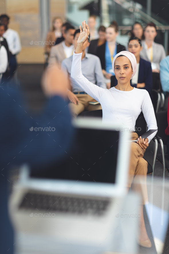 Front view of businesswoman raising hand in a business seminar in office - Stock Photo - Images
