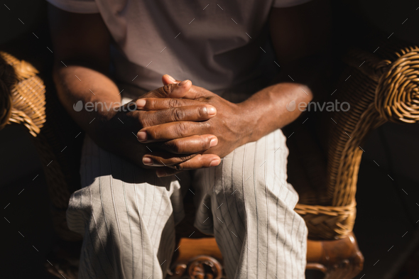Mid section of senior African American man siting on wicker chair with hands clasped at home - Stock Photo - Images