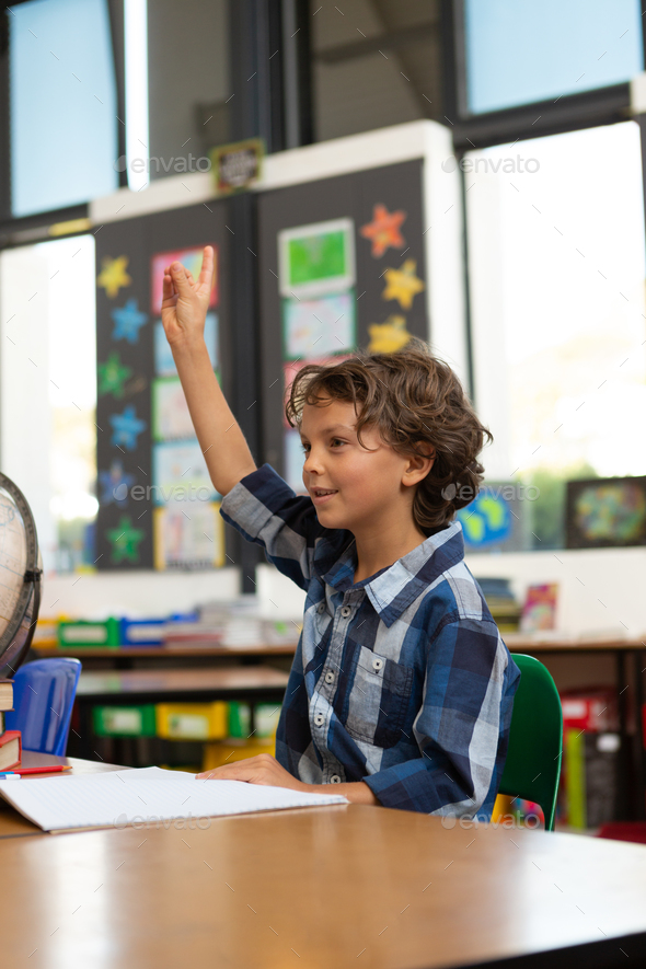 Side view of a Caucasian schoolboy raising his hand while sitting at desk in the classroom at school - Stock Photo - Images