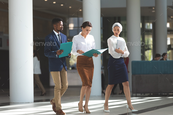 Front view of diverse business people walking with files in their hands in lobby - Stock Photo - Images